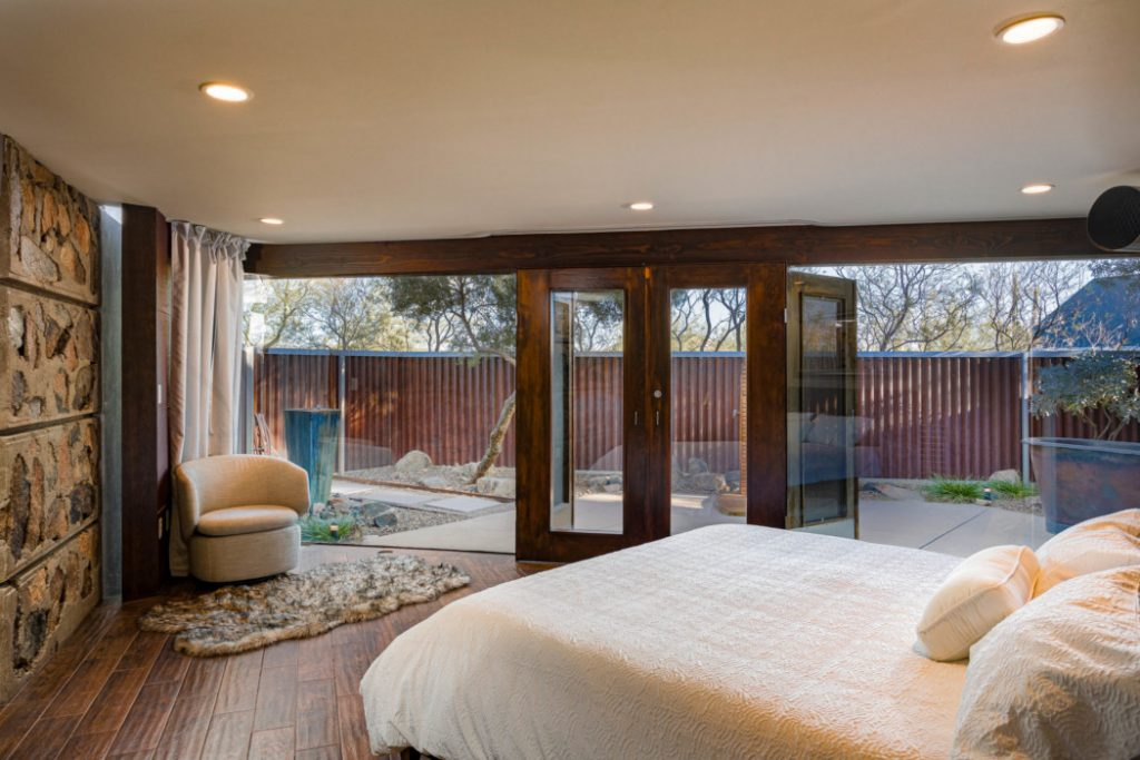 Expansive master bedroom with glass wall to bring the outdoors in.