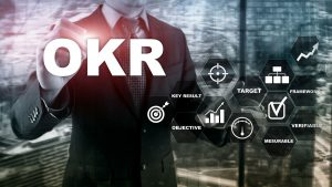 Letters OKR and graphs in front of man in suit
